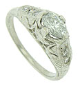 A brilliant .48 carat, H-I color, Vs2 clarity oval cut diamond glows from the face of this antique style engagement ring