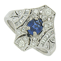 A breathtaking .69 carat oval cut sapphire glows from the center of this phenomenal antique engagement ring