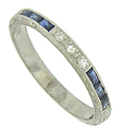 Strings of fine faceted diamonds and square cut sapphires spin across the face of this romantic antique style wedding band