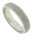 This mens wedding band features a pebble finish center band framed in brightly polished metal