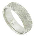 An engraved floral design covers the face of this handcrafted 14K white gold mens wedding band