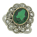 A fantastic oval cut green tourmaline is featured at the center of this fantastic antique engagement ring