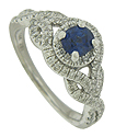 Intertwining vines of fine faceted diamonds spring from the shoulders of this romantic engagement ring to surround a glowing round cut sapphire at its center