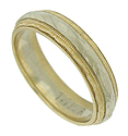 This elegant vintage wedding band is a marriage of hammered white and yellow gold finished in an intricate milgrain design