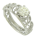 Spectacular organic cutwork frosted with diamonds surrounds a glittering .81 carat, I color, Vvs2 round cut diamond set into this antique style engagement ring