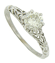Richly carved organic cutwork adorns the shoulders and sides of this magnificent antique style engagement ring