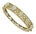 Elegant lacy filigree surrounds five glowing opals set on the surface of this spectacular estate bracelet