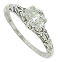 Abstract organic cutwork covers the shoulders and sides of this elegant antique style engagement ring