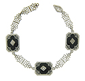 This handsome 14K white gold bracelet features floral inspired links attached to a trio of filigree decorated onyx figures