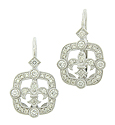 Fashioned of 14K white gold, these antique style earrings feature a diamond frosted fleur de lis figure framed in round cut diamonds