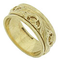 This vintage wedding band is crafted of 14K yellow gold and features a center band decorated with deeply engraved flowers and leaves