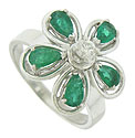 This captivating 14K white gold estate ring features a brilliant emerald and diamond flower set on a wide, brightly polished band