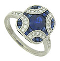 This spectacular platinum engagement ring features a breathtaking pattern of deep blue sapphires and round cut diamonds