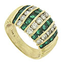 Alternating ribbons of bezel set emeralds and diamonds adorn the face of this 14K yellow gold wedding band