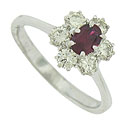 A glowing oval cut ruby is set into this elegant 14K white gold engagement ring