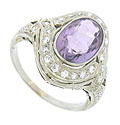 A glittering oval cut amethyst is set into the center of this 18K white gold engagement ring
