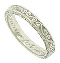 Curling vines are engraved into the face and sides of this elegant antique platinum wedding band