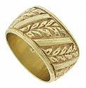 This wide, handsome 14K yellow gold wedding band is covered with diagonal bands of leaves and ribbon