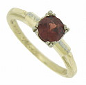 A deep hued garnet is the focus of this vintage 14K yellow gold ring