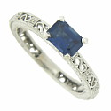A deep blue emerald cut sapphire rises above the surface of this elegant 14K white gold engagement ring