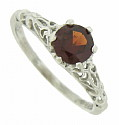This fantastic antique style engagement ring features a round cut garnet and breathtaking organic cutwork mounting