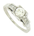 A glittering .35 carat, round cut diamond is set into the center of this handsome 18K white gold antique ring