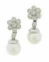 These delicate estate earrings feature a single cultured pearl that dangles from a sparkling diamond set flower