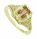 This fantastic 14K yellow gold engagement ring is set with a .82 carat emerald cut andalucite