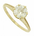 A glittering GIA certified, .94 carat, H colored Si2 colored, round cut diamond is set into the crown inspired central mount of this handsome 14K yellow gold engagement ring