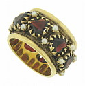 This sparkling 14K yellow gold wedding band is set with seven heart cut faceted garnets