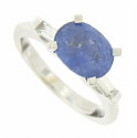 A deep blue 2.50 carat oval cut sapphire appears to float above the face of this 14K white gold engagement ring