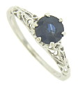 A 1.03 carat round cut sapphire is set into the face of this elegant 14K white gold engagement ring
