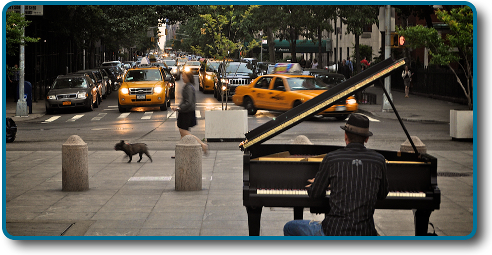 A photograph shows a person playing a piano on the sidewalk near a busy intersection in a city.