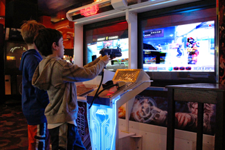 A photograph shows two children playing a video game and pointing a gun-like object toward a screen.