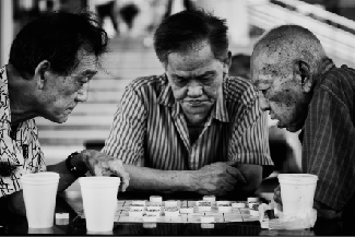A picture shows three people at a table leaning over a board game.
