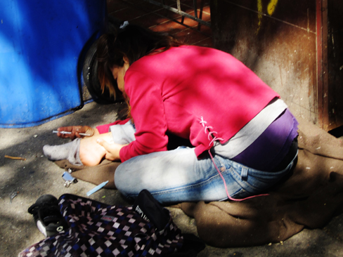 A photograph shows a person injecting heroin intravenously with a hypodermic needle into her ankle.