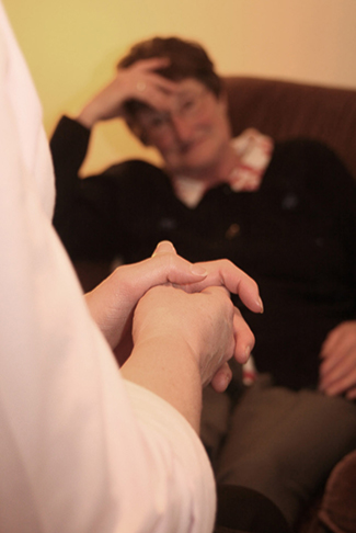 A photograph depicting a woman in a therapy session with her therapist is shown.