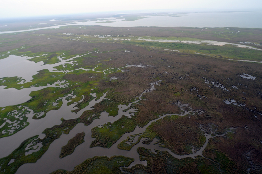 An airplane view of oil-clogged sandbars and the surrounding ocean water tainted by oil is shown here.