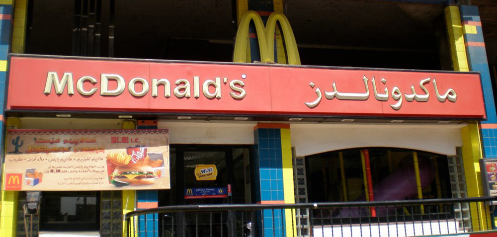 The front of a McDonald's restaurant featuring Arabic writing is shown.