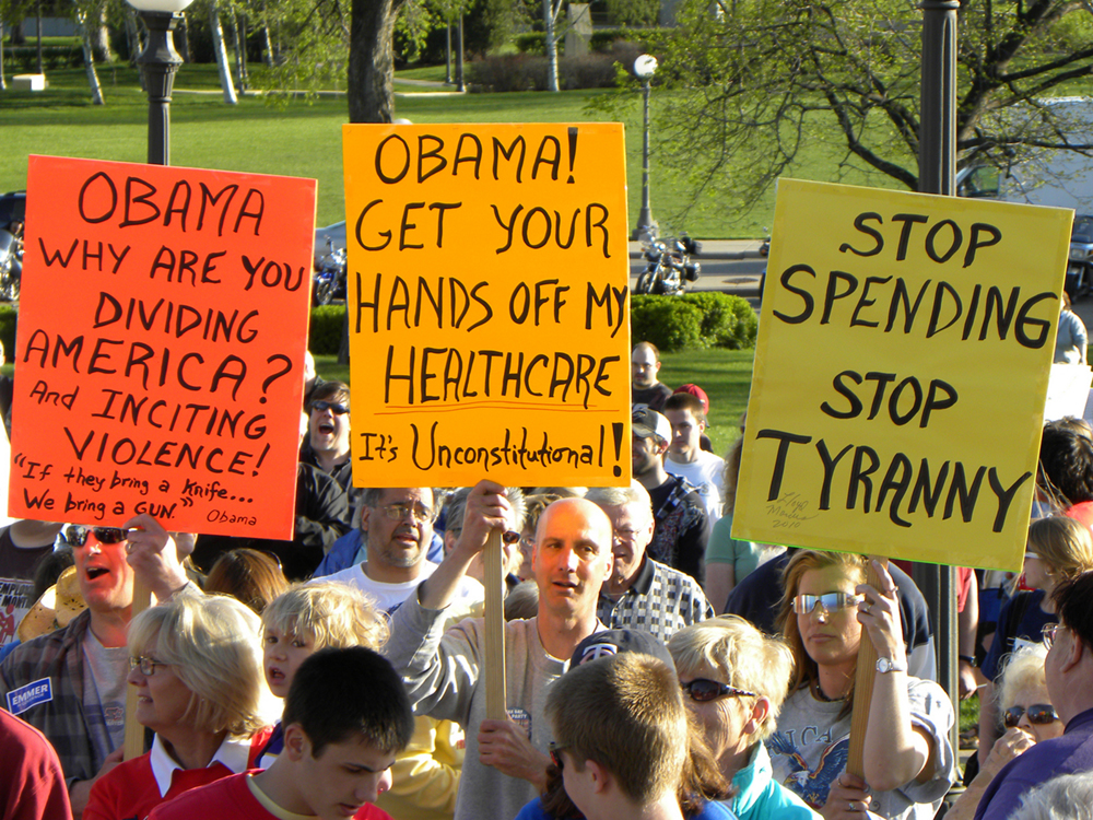 A group of protesters holding signs protesting federal health care changes are shown here.