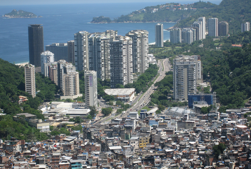 This photo is of a city with large high rises in the background and a slum in the foreground.