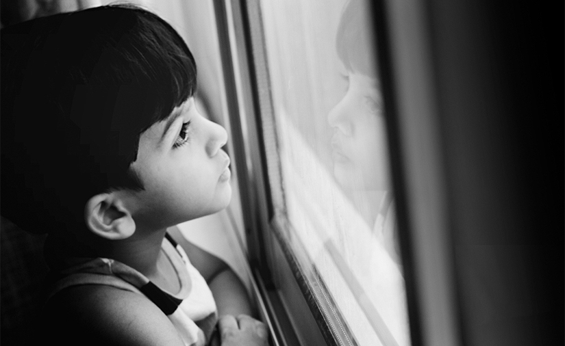 This photo depicts a young boy with dark hair looking out the window.