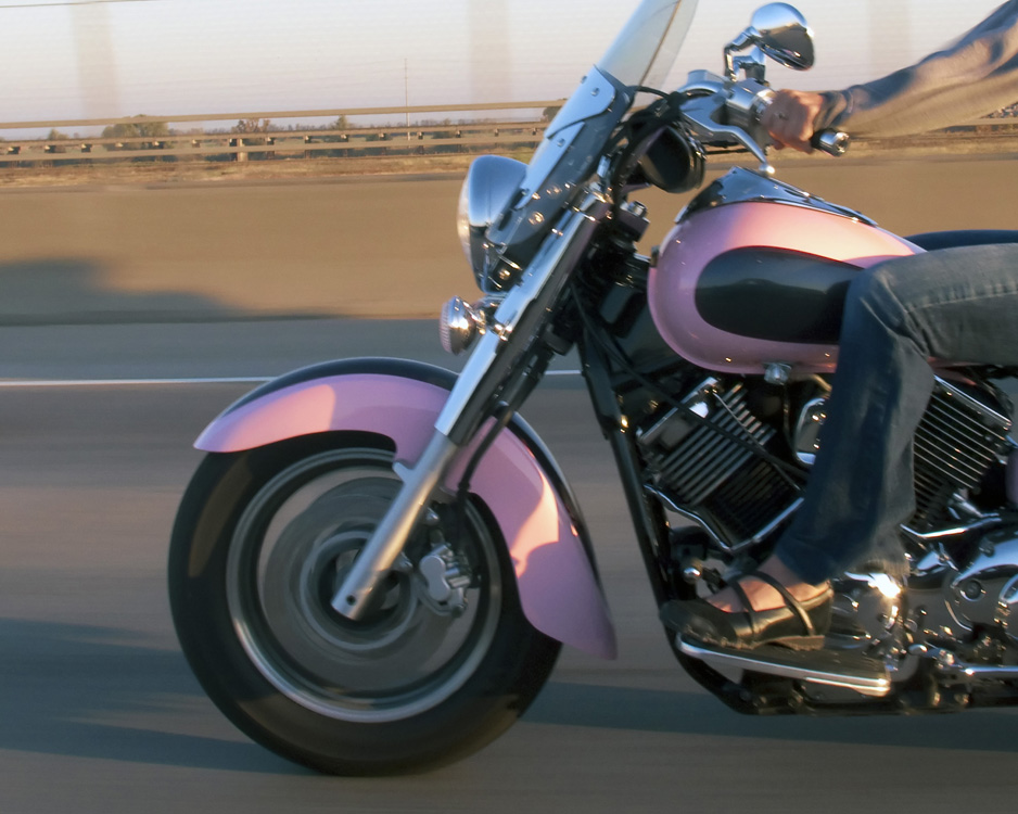 A woman riding a pink motorcycle is shown here.