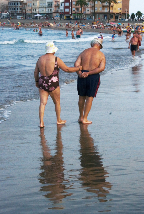 An elderly man wearing blue swim trunks and an elderly woman wearing a flowered bathing suit and hat are shown walking near the water on a beach.