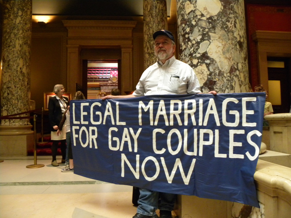 "An older man with a gray beard, wearing a baseball cap, buttoned-up shirt, and jeans, is shown in a marbled lobby with columns holding a blue banner reading ""Legal Marriage for Gay Couples Now."""