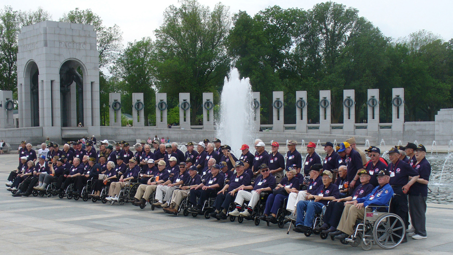 A group of elderly men, many in wheelchairs, all dressed in blue shirts and baseball caps, are shown standing and sitting in a memorial setting, with a fountain and pillars behind them.
