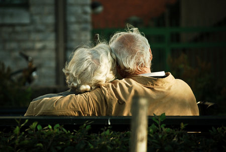 An elderly man and woman are shown from behind sitting on a bench. The man is shown wrapping his arm around the woman's shoulders.