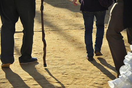 The legs of three men, one using a cane, are shown from behind walking on a dirt surface.