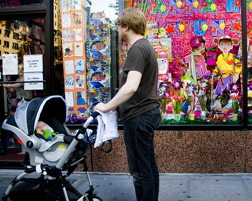 A photo of a man pushing a baby in a stroller down the street