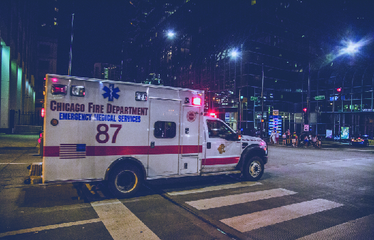 """An image of a truck with flashing lights driving through an intersection. The side of the truck reads """"Chicago Fire Department Emergency Medical Services""""."""